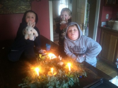 the boys making unethusiastic faces with our lit solstice wreath