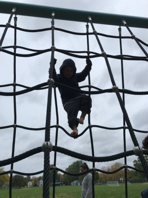 Lijah climbing a tall rope ladded structure