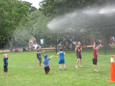 the kids playing in the spray from the firehose