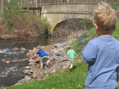 Harvey and Zion poking around a creek, Lijah looking on
