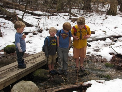 Harvey, Zion, Lijah, and Nathan posing crossing a stream in the snowy woods