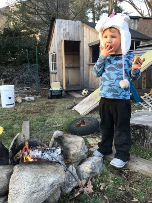 Lijah licking his fingers after eating a smore by the fire