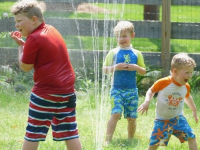 the boys playing in the sprinkler