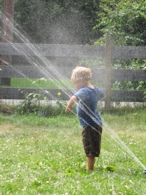 Zion, in his clothes, standing with his back to the sprinkler stream getting soaked