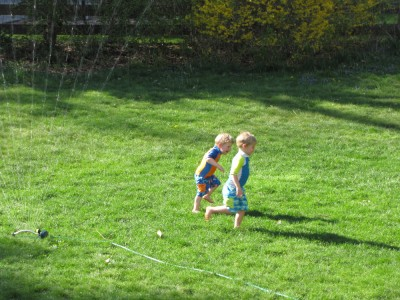 Lijah and Zion running in the sprinkler on the green grass