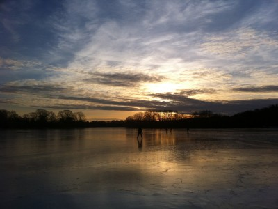 skaters silhouetted by the setting sun on the frozen Spy Pond