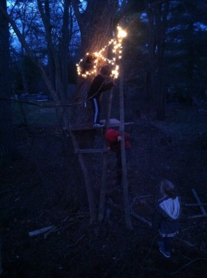 Harvey and two friends playing on a treehouse in the dark