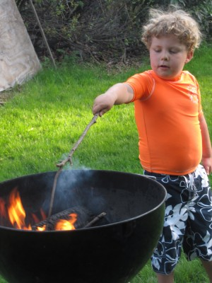 Harvey poking a stick into the fire in the kettle grill