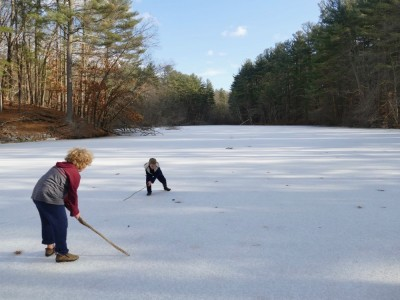 Harvey and Zion on the pond playing hockey with sticks