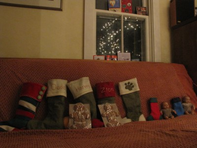 our stockings arrayed on the couch, with gingerbread men for the boys and the tree lights' reflection in the windo