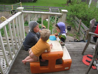 Harvey, Lijah, and Julen at the plastic picnic table on the porch