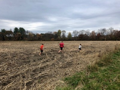 the boys running through a stubbly corn field
