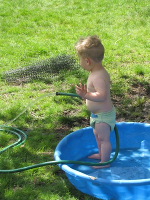 Lijah standing in the wading pool with a hose