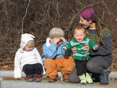 Leah and the three boys sitting on a bridge rail, all in home-made sweaters