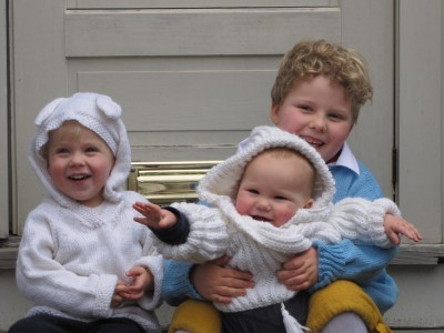 the three boys--Harvey holding Lijah--posing in their new sweaters on Grandpa's front steps