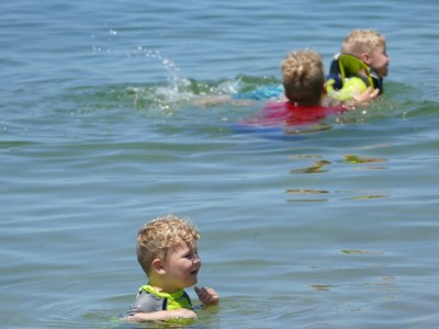 Lijah chest deep in water, Harvey and Zion swimming beyond him