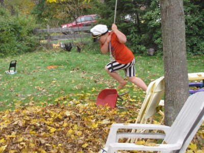 Harvey swinging on a rope into the leaf pile
