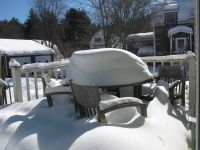 a lot of snow on the table on the back deck