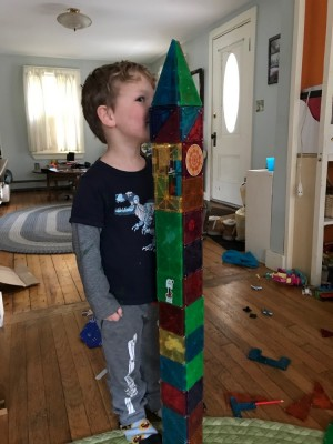 Lijah measuring himself against a Magnetiles building