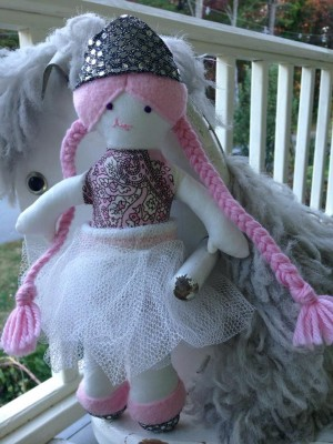 the doll--pink hair, silver crown, dancy skirt--posing on the porch
