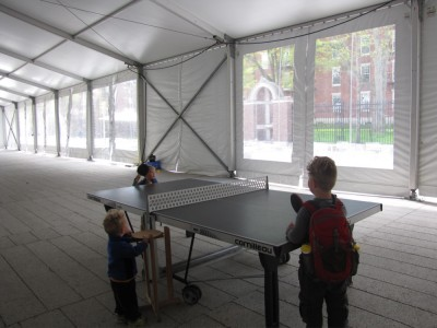 the boys playing ping pong in a giant empty event tent