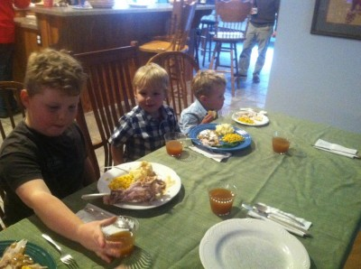 Harvey, Zion, and Lijah sitting at the Thanksgiving board