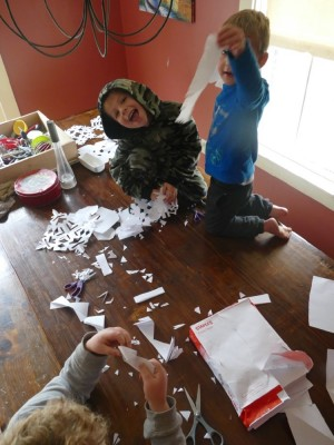 the boys making paper snowflakes at the kitchen table