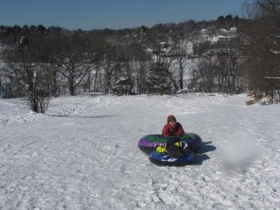 the boys on snow tubes on top of the sledding hill