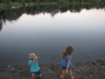 Zion and Taya by the shore of the pond throwing stones