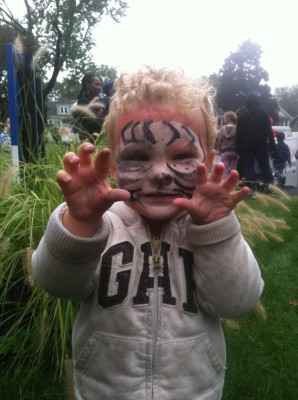 Lijah, face-painted like a tiger, showing his claws