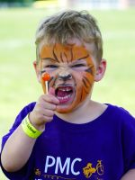 Lijah in tiger face paint roaring while holding a lollipop