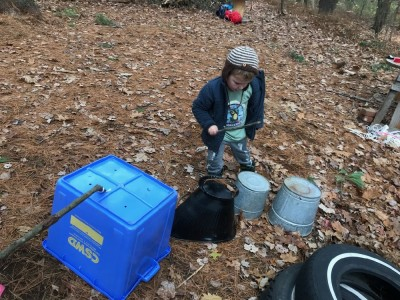 Lijah playing drums on tin buckets in the woods