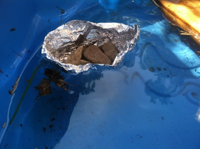 a boat molded out of tinfoil floating, supporting several rocks
