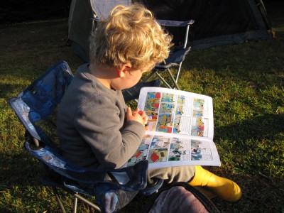 Harvey in his camping chair reading a Tintin book in the early morning sunlight