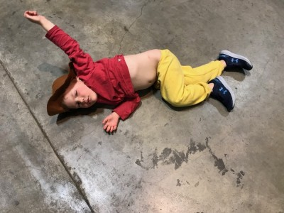 Lijah in a cowboy hat lying on a concrete floor