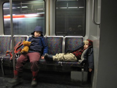 Harvey and Zion on the subway; Zion lying down