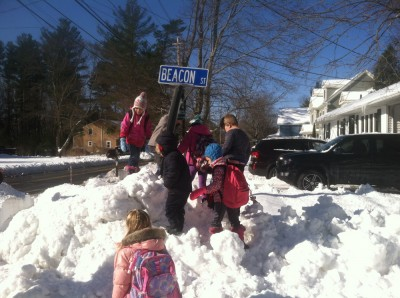 every kid at the bus stop climbing a mountain of snow to touch the street sign