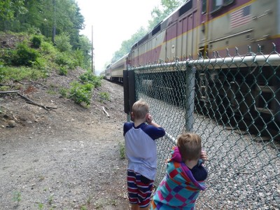 Zion and Lijah holding their ears as a train roars by ten feet away
