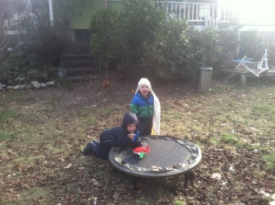 Zion and Lijah playing with toys on the little trampoline