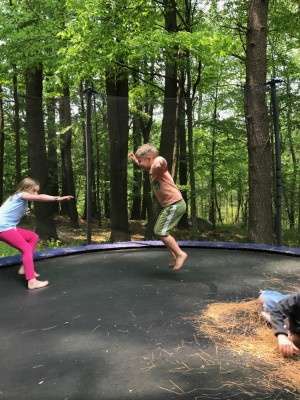 Zion and a friend jumping on a trampoline