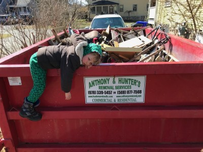 Lijah lying on the rail of the dumpster