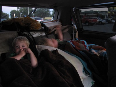 the boys tucked in in the back of the car, at a rest stop
