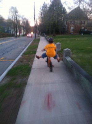 Harvey riding down the twilight street, feet off the pedals