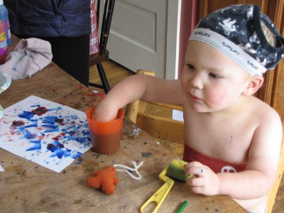Lijah with no shirt and undies on his head working on painting