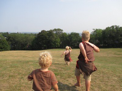 the boys running in a field wearing their historical Wampanoag costumes