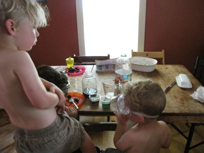 shirtless kids doing chemistry experiments at the kitchen table