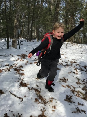 Zion in shirt sleeves running in the snowy woods