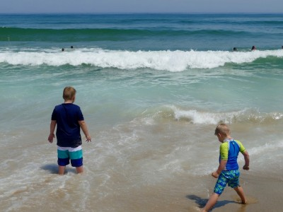 Harvey and Zion standing in the wash of the big waves