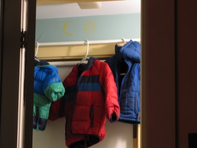 the boys' three coats hanging in the bathroom after the wet snow