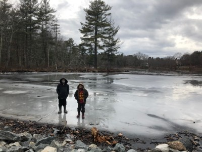 Zion and Lijah standing on the puddley ice on the edge of Fawn Lake